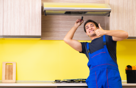Man giving a thumbsup after fixing a kitchen extractor fan