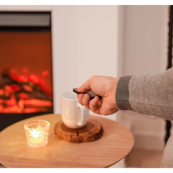 A person controlling an electric fireplace using a remote